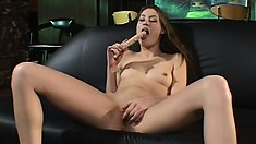 Adorable young babe Jassie lies on the couch and has fun with a dildo